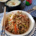 vegetable fried rice in a white bowl with two chopsticks.